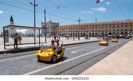 LISBON, PORTUGAL - 31 JULY 2018: Tourists making use of novelty scooters to view the sights of Lisbon on a bright and sunny day in Comercio Square.