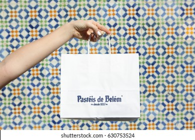 LISBON, PORTUGAL - April 14, 2017: Hand holding paper bag with the famous Pasteis de Belem. The picture was taken with the original bakery tiles background on April 14, 2017 in Belem, Lisbon, Portugal
