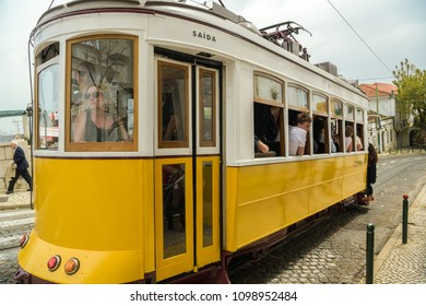 LISBON, PORTUGAL - APRIL 20, 2018: People taking ride in overcrowded tram number 28 in Alfama district in Lisbon, Portugal during April 2018. The tram is popular tourist attraction