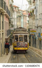 LISBON, PORTUGAL - APRIL 20, 2018: Typical yellow tram number 28 riding through narrow Caveleiros street in Lisbon, Portugal during April 2018
