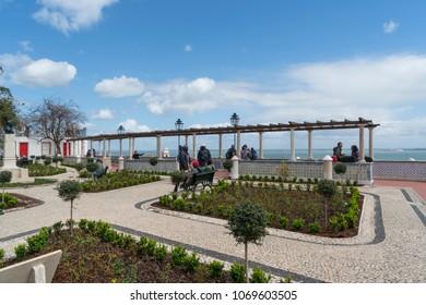 Lisbon, Portugal. April 2018. People look the panorama from Miradouro de Santa Luzia in Lisbon, Portugal