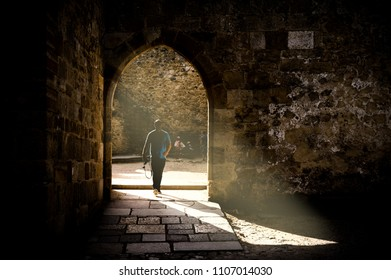 Lisbon, Portugal - April 23, 2018: Man passing through a doorway at Sao Jorge's Castle, one of the main touristic attractions of the city