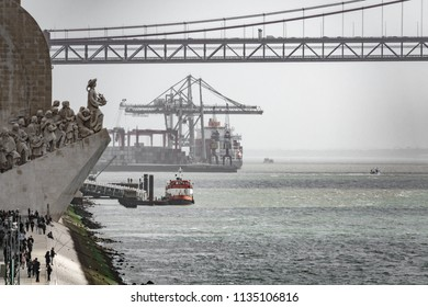 LISBON, PORTUGAL - APRIL 4, 2018: Unidentified tourists visit Monumento aos Descobrimentos with 25th april bridge and port in the background in Lisbon, Portugal
