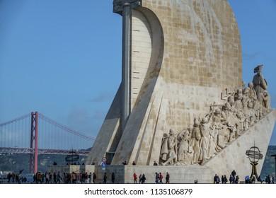 LISBON, PORTUGAL - APRIL 4, 2018: Unidentified tourists visit Monumento aos Descobrimentos with 25th april bridge in the background in Lisbon, Portugal