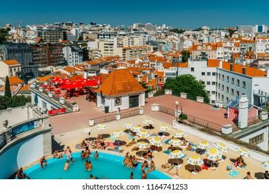 LISBON, PORTUGAL - AUGUST 20, 2017: People Having Fun In Pool On Top Of Lisbon City Skyline Buildings