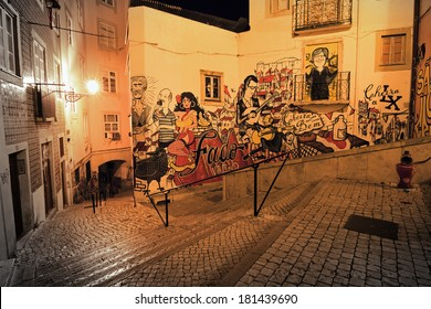 LISBON, PORTUGAL - AUGUST 21, 2013: Typical urban night scene with artwork on the wall in the narrow streets of Lisbon, Portugal, on August 21, 2013