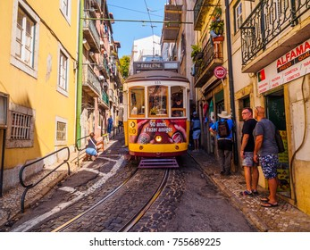 Lisbon, Portugal - August 22, 2017: People stepping away on sidewalk in order to let the street car run in the streets of Lisbon