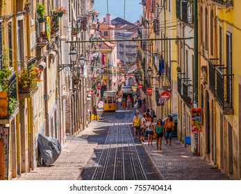 Lisbon, Portugal - August 22, 2017:  Very wide shot of Lisbon slope street, with street car tracks and people walking