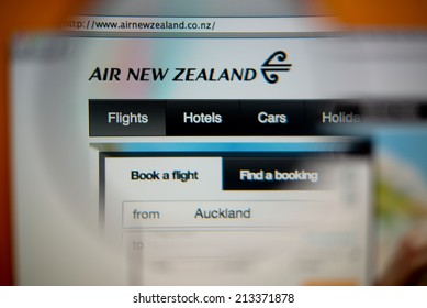 LISBON, PORTUGAL - AUGUST 27, 2014: Photo of Air New Zealand homepage on a monitor screen through a magnifying glass.