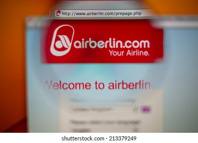 LISBON, PORTUGAL - AUGUST 27, 2014: Photo of Airberlin homepage on a monitor screen through a magnifying glass.