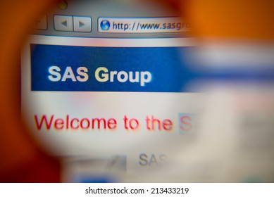 LISBON, PORTUGAL - AUGUST 27, 2014: Photo of the SAS Group homepage on a monitor screen through a magnifying glass.