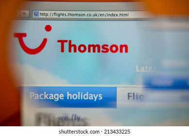 LISBON, PORTUGAL - AUGUST 27, 2014: Photo of Thomson Airways homepage on a monitor screen through a magnifying glass.