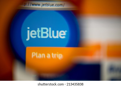 LISBON, PORTUGAL - AUGUST 27, 2014: Photo of JetBlue Airways homepage on a monitor screen through a magnifying glass.