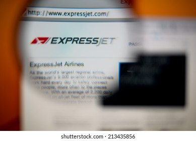 LISBON, PORTUGAL - AUGUST 27, 2014: Photo of ExpressJet Airlines homepage on a monitor screen through a magnifying glass.