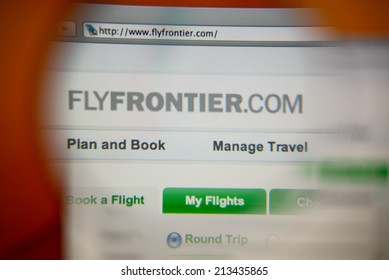 LISBON, PORTUGAL - AUGUST 27, 2014: Photo of Frontier Airlines homepage on a monitor screen through a magnifying glass.