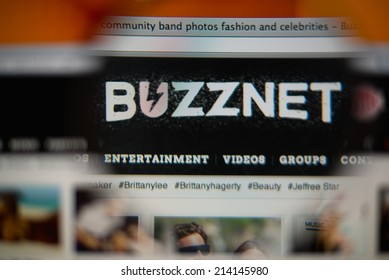 LISBON, PORTUGAL - AUGUST 27, 2014: Photo of BuzzNet homepage on a monitor screen through a magnifying glass.