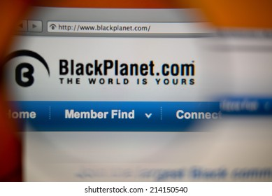 LISBON, PORTUGAL - AUGUST 27, 2014: Photo of BlackPlanet homepage on a monitor screen through a magnifying glass.