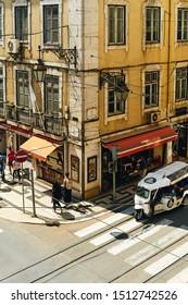 Lisbon, Portugal - August 27, 2019: tuc-tuc transport on the street of old Baixa neighborhood
