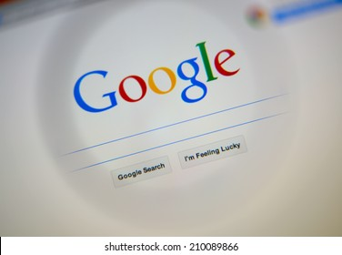 LISBON, PORTUGAL - AUGUST 3, 2014: Photo of Google homepage on a monitor screen through a magnifying glass.