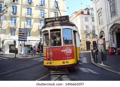 """Lisbon, Portugal. August 31 2019. Lisbon's famous vintage Tram 28 heading from Baixa towards the Alfama District / Old City,  Lisbon Cathedral, Fado Club and Castle """"Sao Jorge"""""""