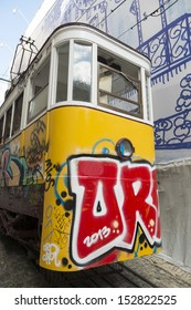 LISBON, PORTUGAL - AUGUST 7: Traditional yellow tram/funicular covered with graffiti. Lisbon on Aug 7, 2013. Trams/funiculars are used to keep the traditional style of the historic center of Lisbon.