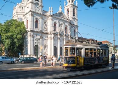 LISBON, PORTUGAL - CIRCA AUGUST 2017: Beautiful view of Estrela Basilica facade and historic yellow tram 28 at tram stop, Lisbon, Portugal.