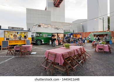 LISBON, PORTUGAL: City cobblestone street with tables of outdoor restaurant and some fast food trucks for hungry customers on 17 May, 2019. Portuguese language has 250 million total speakers