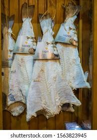 LISBON, PORTUGAL - DEC 08, 2018: cod fish slices hanging on wooden wall at Salt Shop in Salinas de Rio Mario