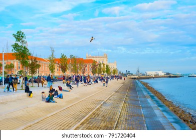 LISBON, PORTUGAL - DECEMBER 10, 2016: People resting on the embankment of Lisbon - famous tourist attraction.