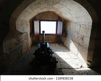 Lisbon, Portugal - December 17th 2017: Ancient cannon inside Belem Tower pointed through an embrasure in the fort wall.