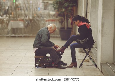LISBON, PORTUGAL - DECEMBER 22 2015: Shoeshine man working on client's shoe on a street in Lisbon, Portugal. Lisbon is very traditional in its ancient streets find shoeshine