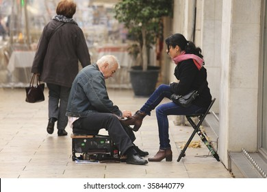 LISBON, PORTUGAL - DECEMBER 22 2015: Shoeshine man unidentified working on client's shoe on a street in Lisbon, Portugal. Lisbon is very traditional in its ancient streets find shoeshine