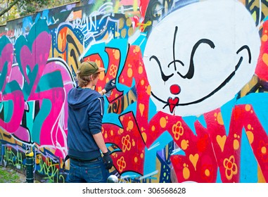 LISBON, PORTUGAL - DECEMBER 23, 2014: Teenager painting graffiti on the wall in Lisbon. Along with London, Berlin, New York, Lisbon is one of the world's great cities for graffiti and street art