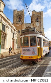 LISBON, PORTUGAL - December 27, 2017:Lisbon yellow tram transportation moving in front of santa maria church.