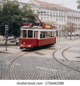 LISBON, PORTUGAL - DECEMBER 31, 2019. Lisbon, Portugal. Vintage red retro tram on street tramline in Alfama district of old town. Popular touristic attraction of Lisboa city. Public tramways trasport.