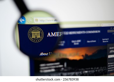 LISBON, PORTUGAL - December 9, 2014: Photo of the American Battle Monuments Commission (ABMC) homepage on a monitor screen through a magnifying glass.