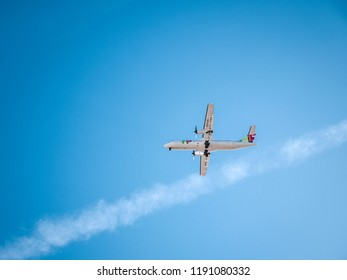 LISBON, PORTUGAL - FEB 10, 2018: From below shot of big white plane flying high in blue sky Tap Express TAP Air Portugal ATR 72-600