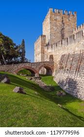 Lisbon, Portugal - February 01, 2017: Castelo de Sao Jorge aka Saint George Castle. Entrance of the Castelejo aka keep with the moat, watchtowers, battlements, ramparts.