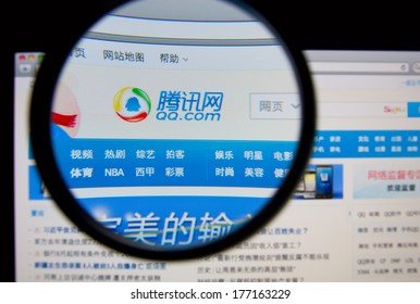 LISBON, PORTUGAL - FEBRUARY 17, 2014: Photo of QQ homepage on a monitor screen through a magnifying glass. QQ is an instant messaging software service. QQ also offers a variety of services.