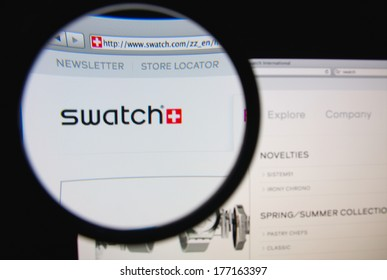 LISBON, PORTUGAL - FEBRUARY 17, 2014: Photo of Swatch homepage on a monitor screen through a magnifying glass.