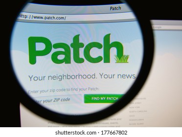 LISBON, PORTUGAL - FEBRUARY 19, 2014: Photo of Patch homepage on a monitor screen through a magnifying glass. Patch.com is an independent US local news and information platform.
