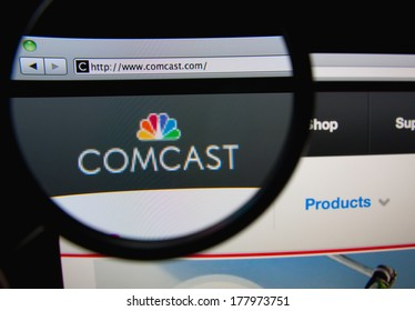 LISBON, PORTUGAL - FEBRUARY 21, 2014: Photo of Comcast Corporation homepage on a monitor screen through a magnifying glass.