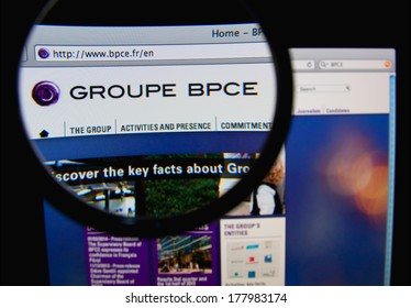 LISBON, PORTUGAL - FEBRUARY 21, 2014: Photo of Groupe BPCE homepage on a monitor screen through a magnifying glass.