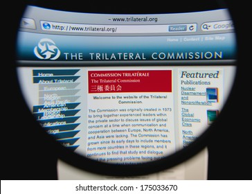 LISBON, PORTUGAL - FEBRUARY 5, 2014: Photo of the Trilateral Commission homepage on a monitor screen through a magnifying glass.
