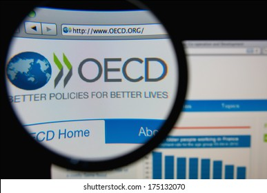 LISBON, PORTUGAL - FEBRUARY 6, 2014: Photo of Organisation for Economic Co-operation and Development homepage on a monitor screen through a magnifying glass.