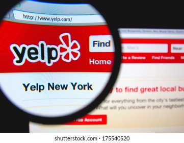 LISBON, PORTUGAL - FEBRUARY 8, 2014: Photo of Yelp homepage on a monitor screen through a magnifying glass.