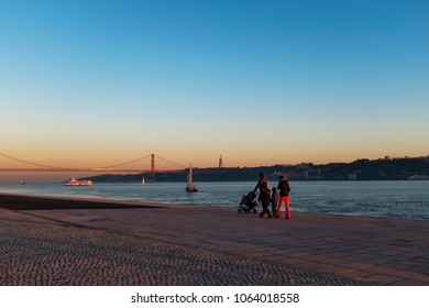 Lisbon, Portugal - January 10, 2017: Family enjoying the sunset near the Tagus River with the 25 of April Bridge (Ponte 25 de Abril) on the background, in the city of Lisbon, Portugal