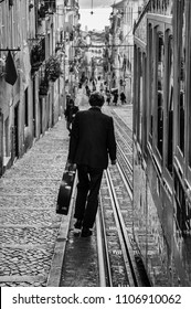 Lisbon, Portugal - January 23, 2010: Stree scene in the city of Lisbon with a man carrying a guitar case walking down the Bica street.