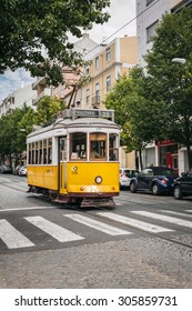 LISBON, PORTUGAL - JULY 17: Famous yellow tram close to crosswalk in Campo de Ourique district, Lisbon, Portugal on July 17, 2015.