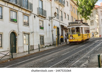 LISBON, PORTUGAL - JULY 2, 2019:  Tram on the hilly area of old town, Sao Tome street in Alfama district is the part of the tourist route with numerous cafes and coffee houses.